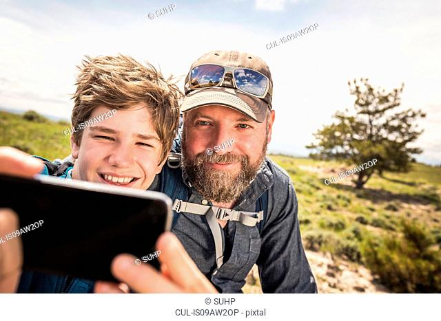 Close up of father and teenage son taking smartphone selfie on hiking trip, Cody, Wyoming, USA