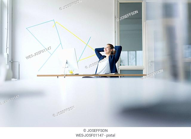 Businesswoman sitting at desk in her office with hands behind head