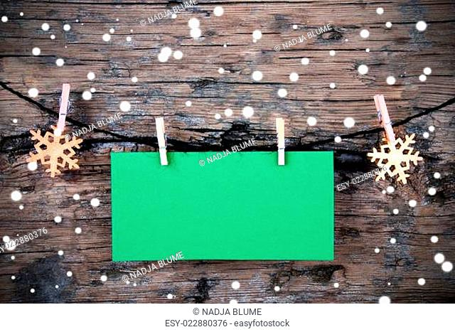 Empty Green Label with Snow on Wooden Background