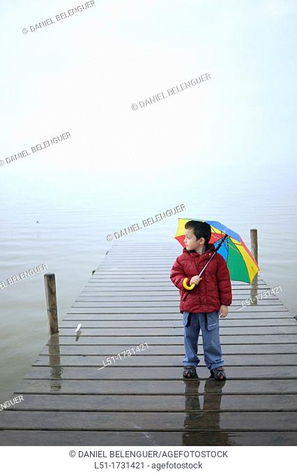 boy with multicoloured umbrella under the raoin by a lake, Albufera de Valencia Nature reserve, Valencia, Spain