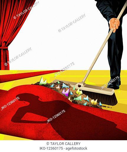 Man sweeping the dirt under the celebrity red carpet