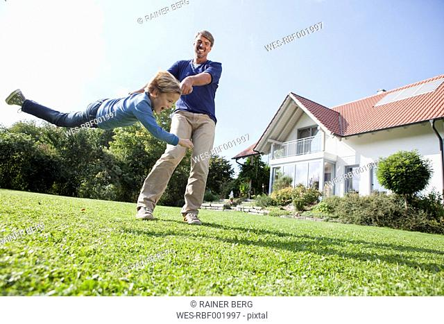 Father playing with son in garden