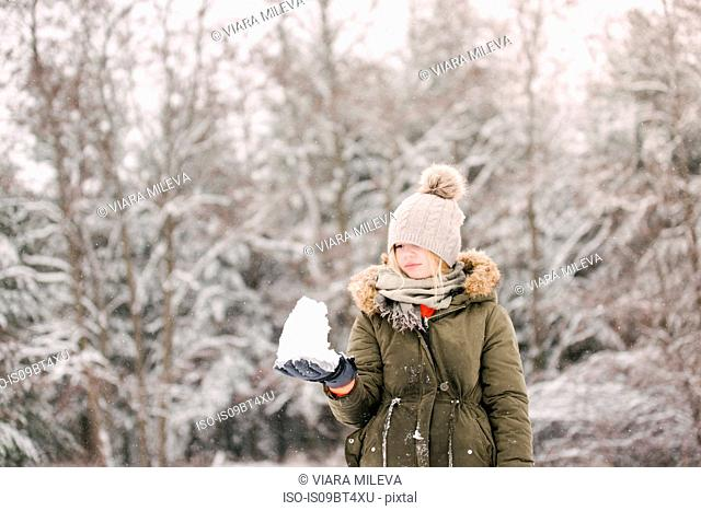 Girl with snow ball in winter landscape