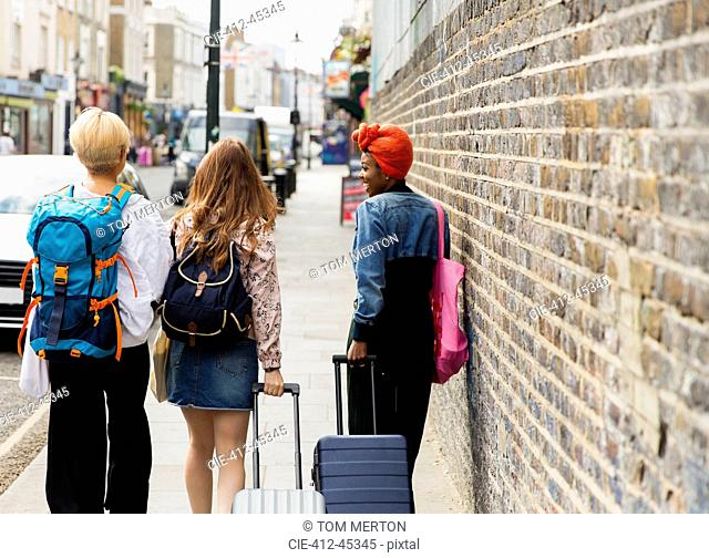 Young women friends with suitcases and backpack walking on urban sidewalk