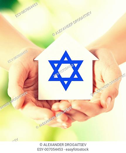 religion, judaism and charity concept - close up of woman hands holding house with star of david over green background