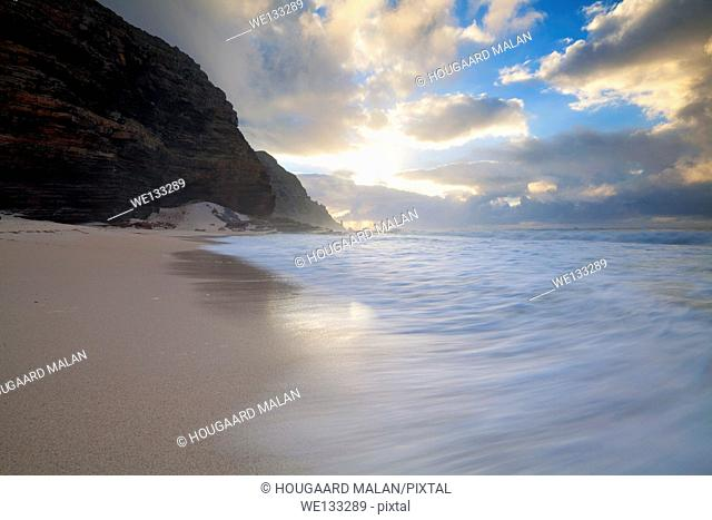 Wide angle landscape photo of a wave washing over Diaz beach under a dramatic sunrise sky. Cape Point National Park, Cape Town, South Africa