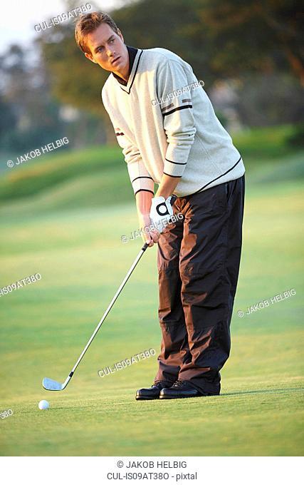 Golfer holding golf club preparing to take gold swing, looking away
