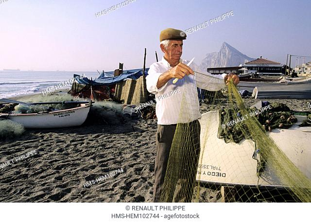 Spain, Andalusia, Linea de la Conception, fisherman on the beach (Gibraltar Rock behind)