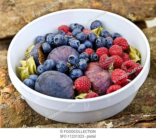A fruit bowl with figs, blueberries and raspberries on a wooden surface