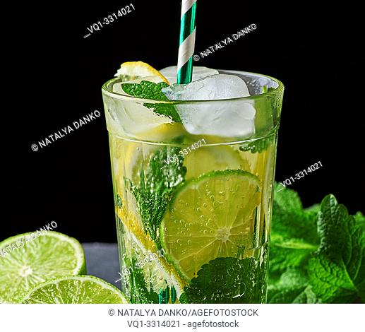 cold lemonade made from fresh lemons, lime, green mint and pieces of ice in a glass on a black background, close up