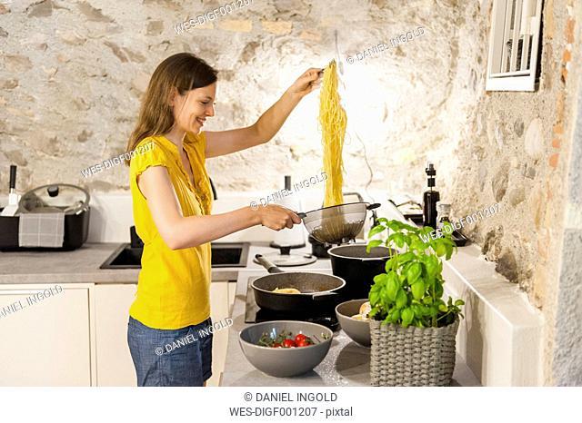 Woman in kitchen preparing spaghetti