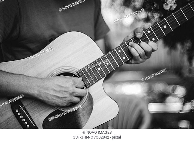 Young Man's Hands Playing Acoustic Guitar