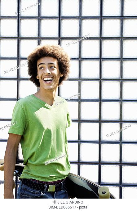 Laughing mixed race teenager carrying skateboard