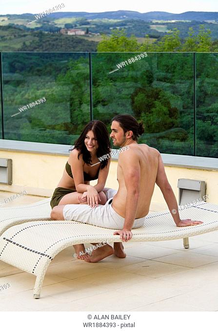 Italy, Tuscany, Young couple relaxing by pool