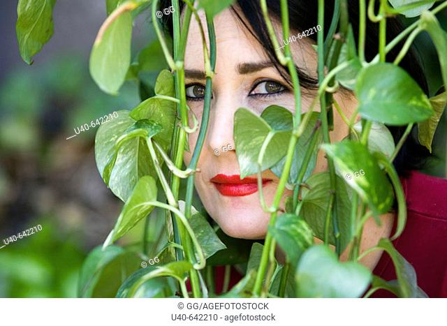Woman looking through ivy