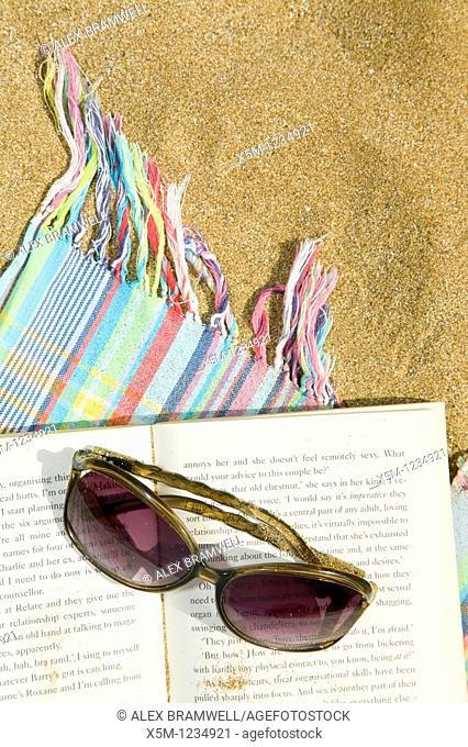 Sunglasses and novel on a beach towel
