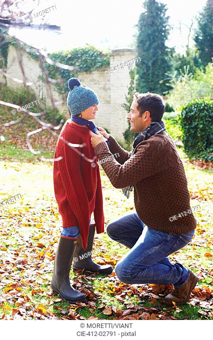 Father tying son's scarf outdoors