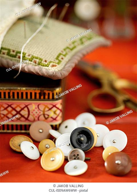 Vintage buttons and pin cushion on red table