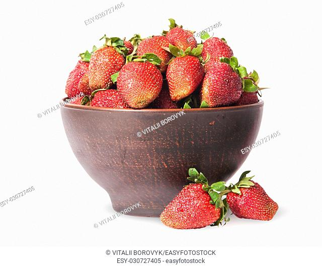 Ripe juicy strawberries in a ceramic bowl and two near isolated on white background