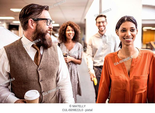 Businessmen and women walking and talking in office