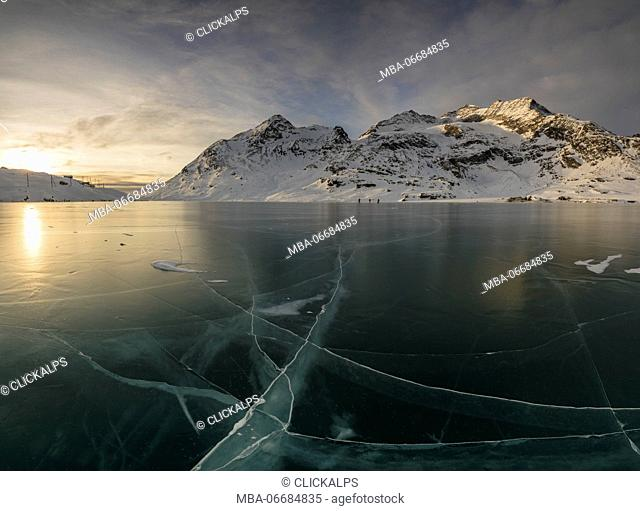 The frozen surface of Lago Bianco framed by snowy peaks at dawn Bernina Pass canton of Graubünden Engadine Switzerland Europe