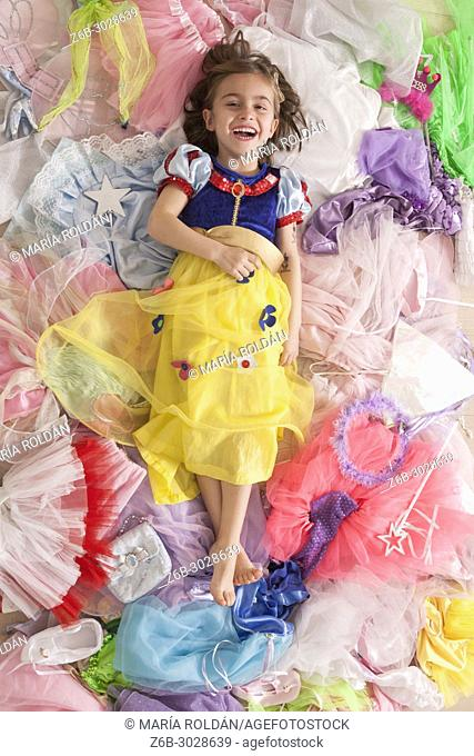 Little girl dressed up like SnowWhite and surrounded by many little girl's princess costumes
