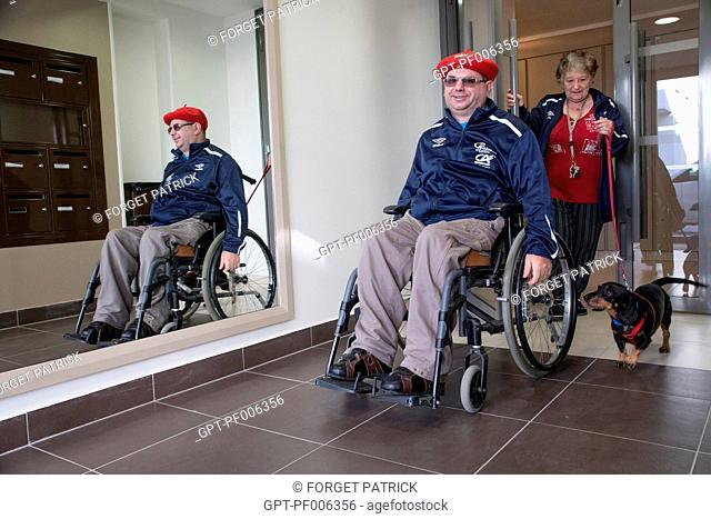 PHYSICALLY HANDICAPPED MAN IN HIS WHEELCHAIR IN A BUILDING'S ENTRANCE, CHARTRES (28), FRANCE