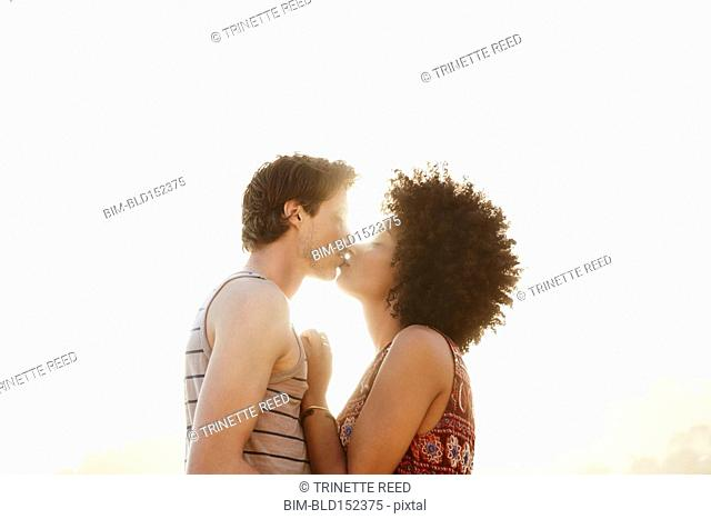 Low angle view of back lit couple kissing