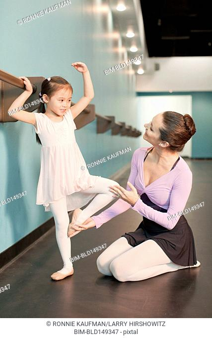 Girl taking ballet lessons from teacher
