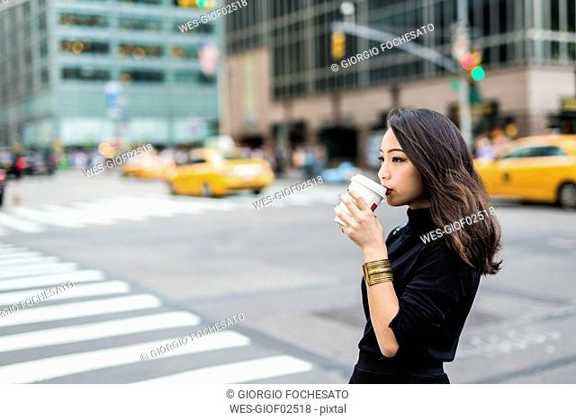 USA, New York City, Manhattan, young woman drinking coffee to go on the street