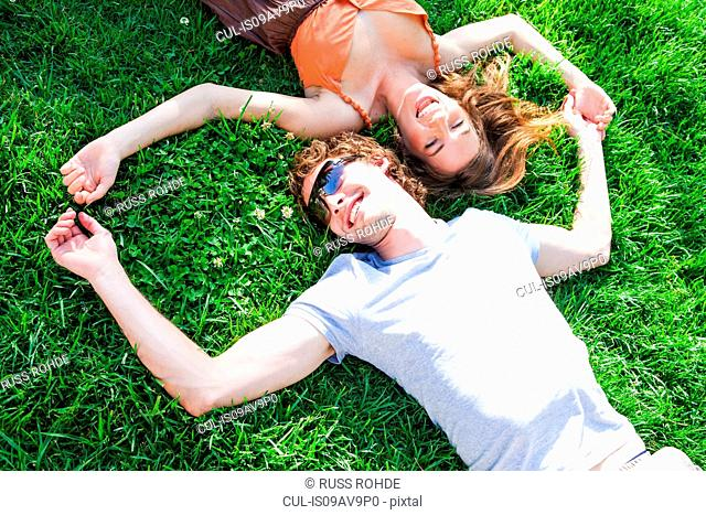 Overhead view of romantic young couple lying on garden lawn