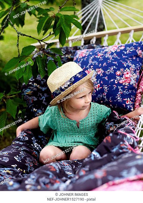 Girl wearing straw hat on hammock