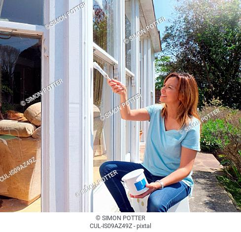 Woman painting window frame