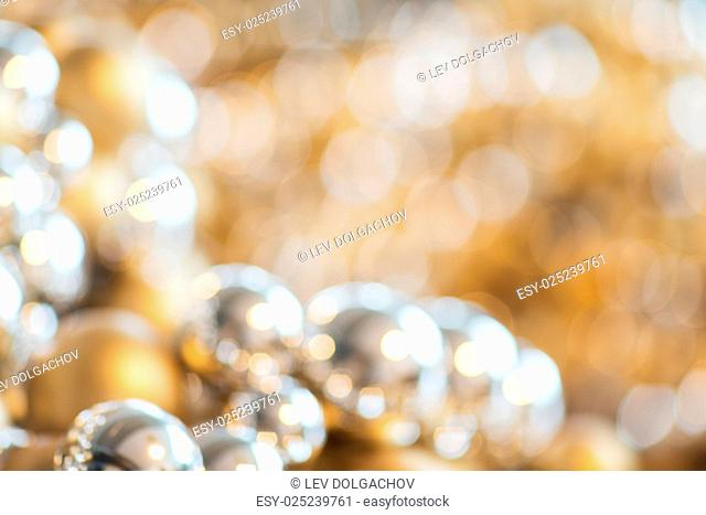 holidays, luxury, decoration and background concept - blurred christmas balls or beads bokeh