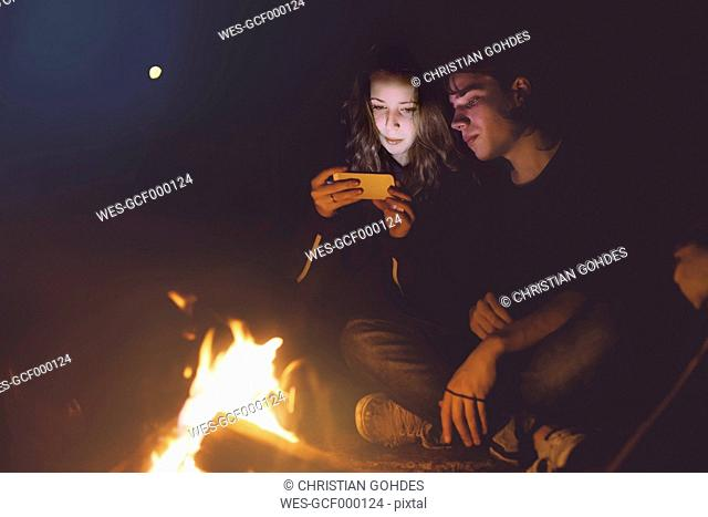 Young couple sitting together at the campfire looking at cell phone