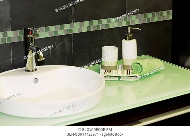 Soap dispenser and a towel on a bathroom sink