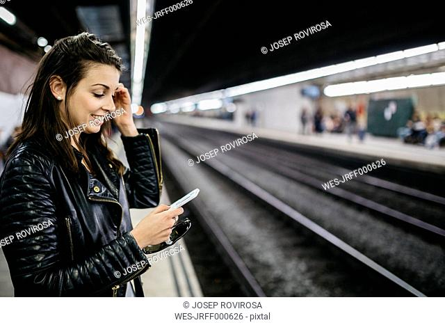 Smiling young woman on train station looking on cell phone