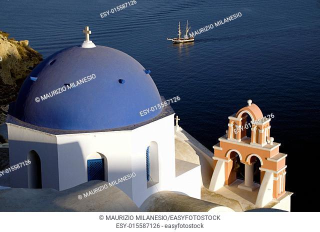 Traditional church in Oia Santorini Greece view of a sailing ship in the Caldera