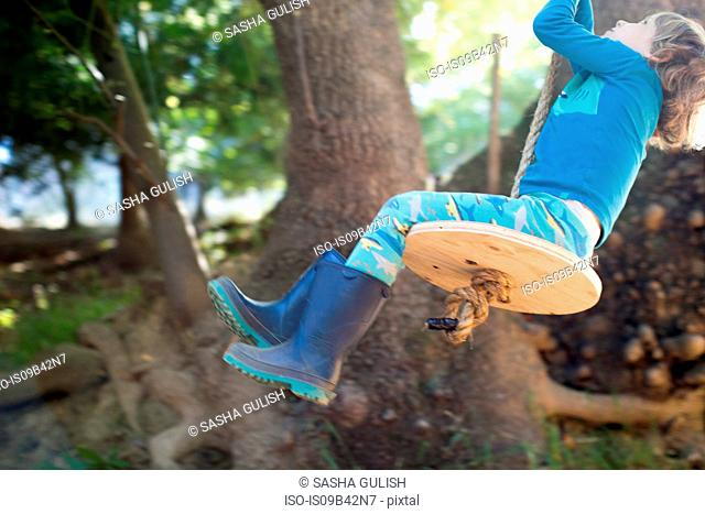 Young boy outdoors, swinging on rope swing