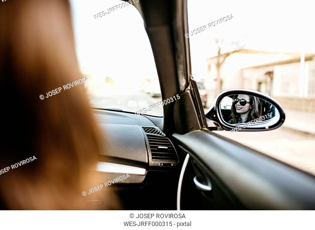 Female front passanger in car reflected in car mirror