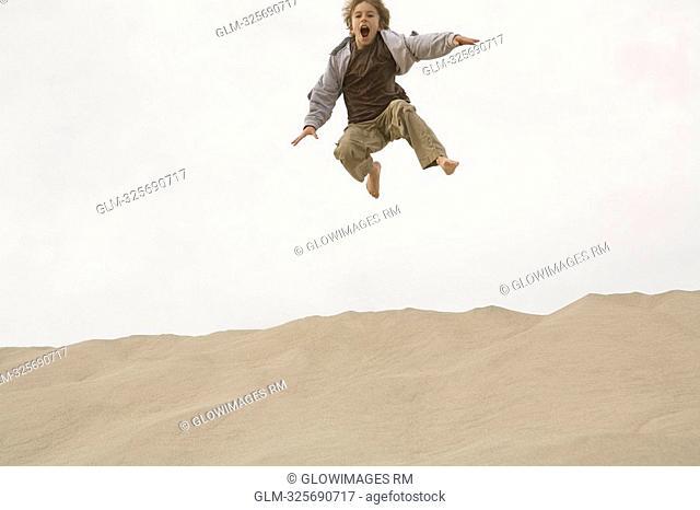 Boy jumping on the beach