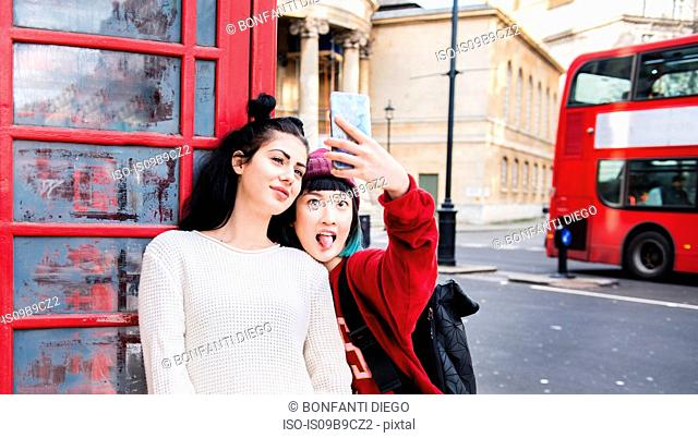 Two young stylish women taking smartphone selfie by red phone box, London, UK