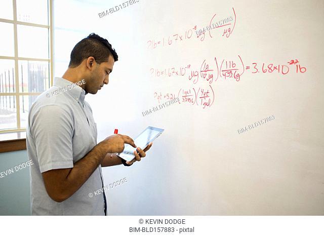 Asian businessman using digital tablet at whiteboard