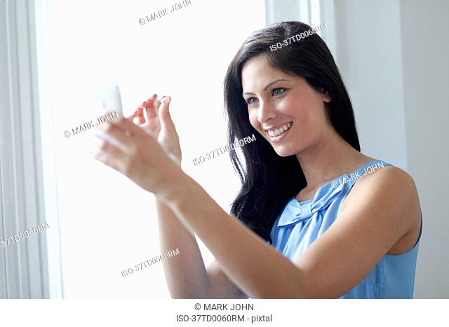 Woman showing off ring on cell phone