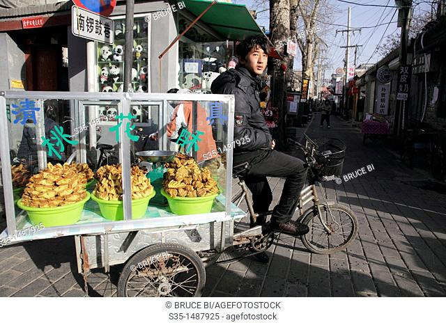 A young man selling Halal dessert on the street of Nan Luo Gu Xian South Luo Gu Lane the new trendy area for the bars, restaurants and boutiques  Beijing  China