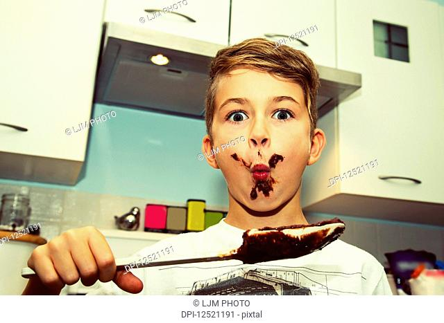 A young boy with a messy face licks the chocolate from the spatula after making fudge; Langley, British Columbia, Canada