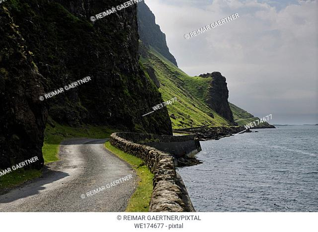 Steep cliffs and rock wall of narrow Highway B8035 on the shore of Loch Na Keal on the Isle of Mull Scotland UK