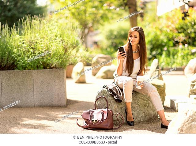 Young businesswoman reading smartphone text in city park
