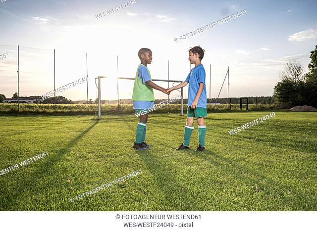 Young football players shaking hands on football ground