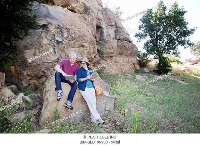 Caucasian couple using digital tablet in remote area